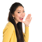 Asian woman shouting. Asian woman holding hand beside her cheek and shouts an announcement, isolated on white background Royalty Free Stock Photos