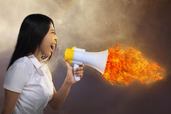 Asian Woman Shouting Megaphone On Fire Royalty Free Stock Photos