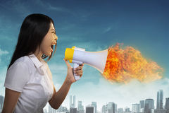 Asian Woman Shouting Megaphone On Fire Royalty Free Stock Photography
