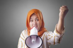 Asian woman Shouting with Megaphone. Young Asian woman wearing hijab shouting with megaphone and pointing to camera. Leader or supporter concept. Close up body royalty free stock image