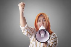 Asian woman Shouting with Megaphone. Young Asian woman wearing hijab shouting with megaphone and pointing to camera. Leader or supporter concept. Close up body royalty free stock photo