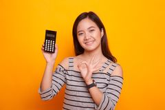 Asian woman show OK with calculator. Royalty Free Stock Photography