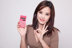 Asian woman show OK with calculator. Stock Photo
