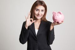 Asian woman show OK  with pig coin bank. Royalty Free Stock Photography