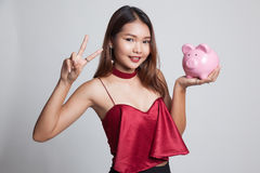Asian woman show victory sign with pig coin bank. Royalty Free Stock Photo