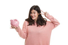 Asian woman show victory sign with pig coin bank. Stock Photo