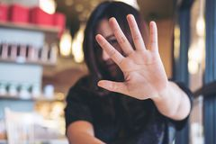An Asian woman showing her hand sign cover her face to say no to someone with feeling angry. In restaurant stock photo