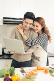Asian woman showing something on the laptop to her boyfriend in Stock Images