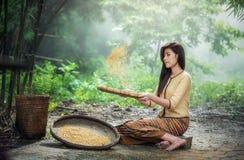 Asian woman sifting grain