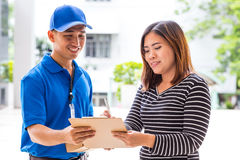 Asian woman signing receipt of delivered package Stock Photos