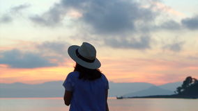 Asian Woman silhouette with hat Enjoying Seascape during Sunrise. beautiful tropical beaches and landscape stock video