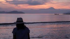 Asian woman silhouette at sunrise ocean pink and orange sky. Asian woman silhouette sunrise ocean pink and orange sky Stock Photo