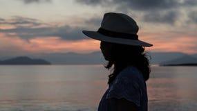 Asian woman silhouette at sunrise ocean pink and orange sky. Asian woman silhouette sunrise ocean pink and orange sky Stock Images