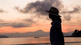 Asian woman silhouette at sunrise ocean pink and orange sky. Asian woman silhouette sunrise ocean pink and orange sky Royalty Free Stock Photos