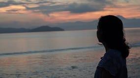Asian woman silhouette at sunrise ocean pink and orange sky. Asian woman silhouette sunrise ocean pink and orange sky Stock Photography