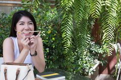 Asian woman sit at outdoor cafe. young female adult with natural. Attractive asian woman sit at outdoor cafe. young female adult with natural make-up hold pencil Royalty Free Stock Image