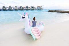 Asian woman sit on pegasus pool float at Maldives. Asian woman sit on pegasus pool float at Maldives beach Royalty Free Stock Photo