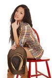 Asian woman sit red chair wearing plaid Royalty Free Stock Photos