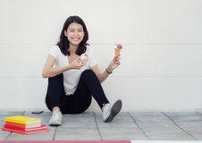 Asian woman sit and relax with ice cream. In university road Stock Photo