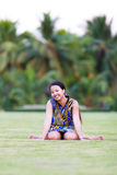 Asian woman sit and smile in park Stock Photo