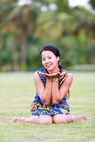 Asian woman sit and smile in park Royalty Free Stock Image