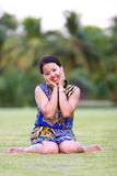 Asian woman sit and smile in park Stock Image