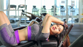 Asian woman sit ups fitness sport gym. Asian woman doing sit ups fitness exercise at sport gym Royalty Free Stock Photography