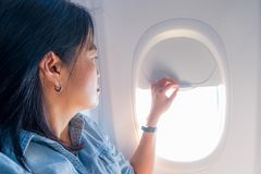 Free Asian Woman Sitting At Window Seat In Airplane And Close The Win Royalty Free Stock Photography - 99681487