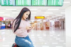 Asian woman sitting on the baggage use of mobile phone check in online ticket airline at international airport Royalty Free Stock Photos