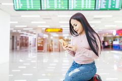 Asian woman sitting on the baggage use of mobile phone check in online ticket airline at international airport Stock Images