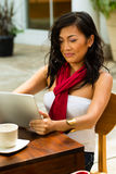 Asian woman is sitting in a bar or cafe outdoor. And is surfing the internet with a tablet computer royalty free stock images