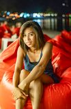Asian woman sitting on Bean bag Background ocean and lights at night royalty free stock image