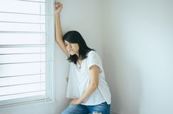 Asian woman sitting on bedroom at home,Female feeling unhappy and confused problem in personal life,Unexpected pregnancy concept royalty free stock image
