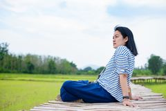 Asian woman sitting cross leg on bamboo bridge at rice field at. Evening time feel relax and fresh with clam emotion.natural travel Stock Photography