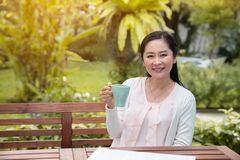 Asian woman sitting with cup of coffee at home garden stock images