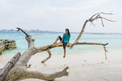 Asian woman sitting on dead tree at the beach with city at background. Maldives royalty free stock photos