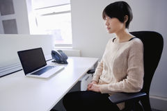 Asian woman sitting at desk with laptop while looking away Royalty Free Stock Images