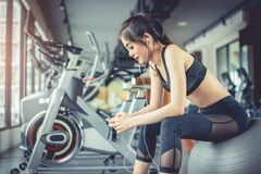 Asian woman sitting on fitness ball and listening music in fitness training gym with smart phone. Relax and sport workout royalty free stock photography
