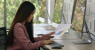 Asian woman sitting in front of group of computer. Asian businesswoman sitting in front of group of computer, using it and looking and reading for graph in stock video