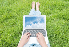 Asian woman sitting on grass floor in the garden textured background for use a notebook computer with blue sky in screen of notebo Stock Image
