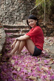 Asian woman sitting on ground with paper flowers Royalty Free Stock Photo