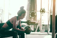 Asian woman sitting at gym club and listen music with relaxing a Royalty Free Stock Image