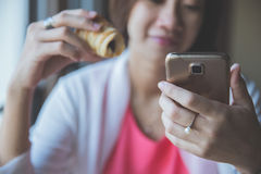 Asian woman sitting hold a bread while using her handphone Stock Photos