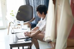 Asian woman working on laptop from home as freelancer stock images
