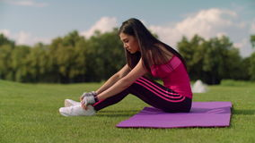Asian woman sitting on mat and tying shoelaces in summer park. Fitness woman preparing for fitness training. Asian girl tying laces on her running sneakers stock video