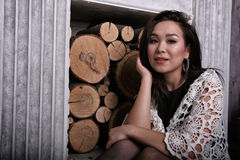 Asian woman sitting near fireplace with shawl on her shoulders stock photos