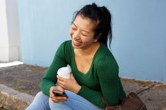 Asian woman sitting outside with mobile phone and smiling Royalty Free Stock Images