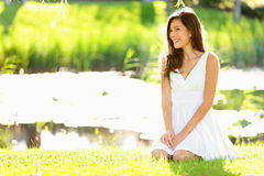 Asian woman sitting in park in spring or summer. Beautiful young woman smiling happy wearing white sundress sitting down in grass in park, Cute mixed race Stock Image