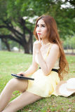 Asian woman sitting in the park and thinking. Royalty Free Stock Photo