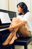 Asian woman sitting at the piano Stock Photo